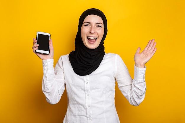 Vrolijke blije jonge vrouw in hijab houdt een telefoon op een geel.