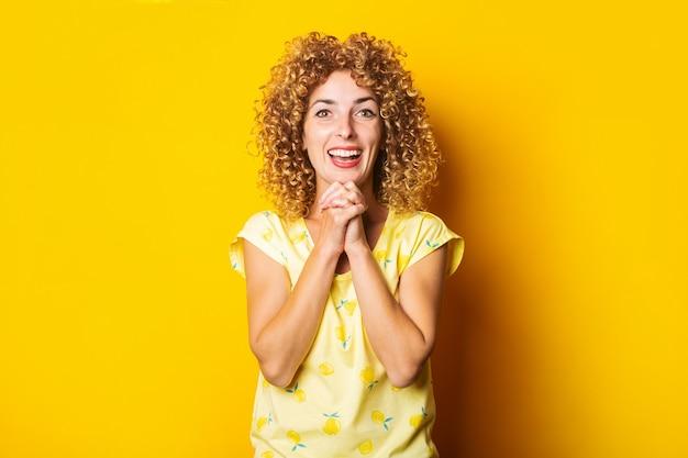 Vrolijke blije verrast curly-haired jonge vrouw op een gele achtergrond
