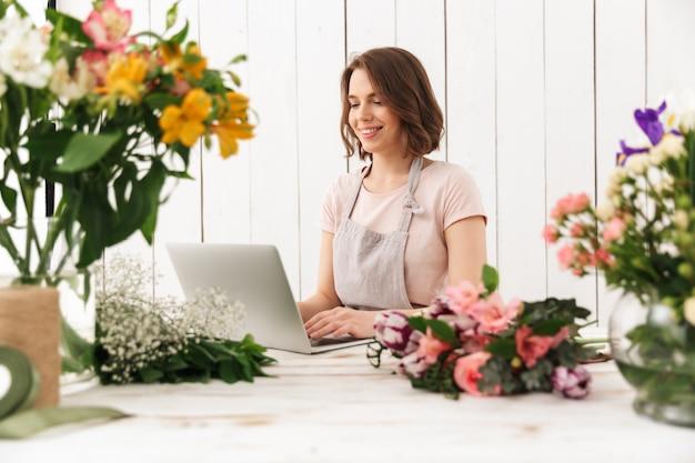 Vrolijke bloemistdame die zich met bloemen bevinden die laptop computer met behulp van.