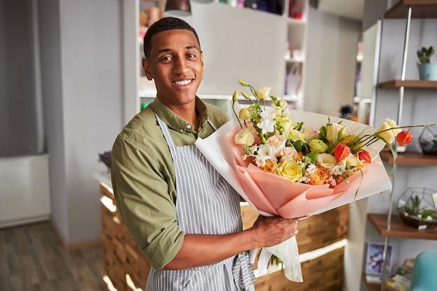 Vrolijke bloemsierkunstenaar met een bos kleurrijke bloemen in een verpakking