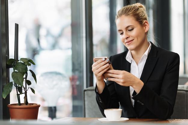 Vrolijke blonde bedrijfsvrouw die mobiele telefoon met behulp van
