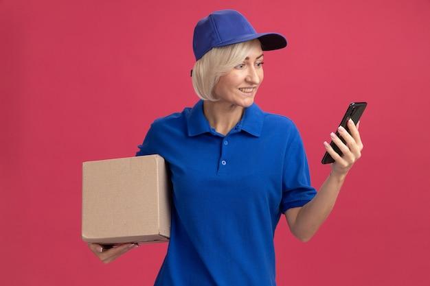 Vrolijke blonde bezorger van middelbare leeftijd in blauw uniform en pet met kartonnen doos en mobiele telefoon die naar de telefoon kijkt