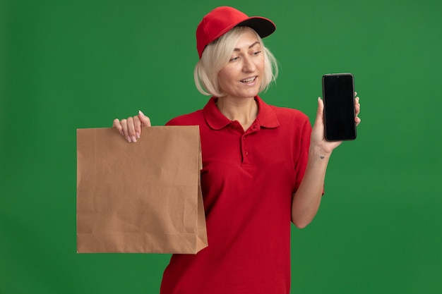 Vrolijke blonde bezorger van middelbare leeftijd in rood uniform en pet met papieren pakket en mobiele telefoon die naar de telefoon kijkt