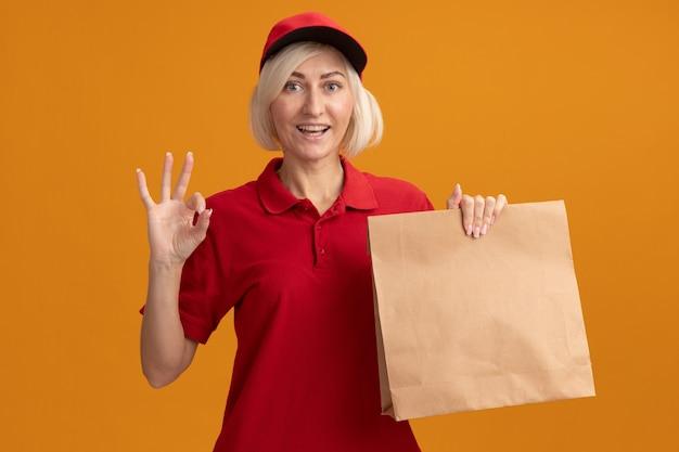Vrolijke blonde bezorger van middelbare leeftijd in rood uniform en pet met papieren pakket met drie met hand geïsoleerd op oranje muur