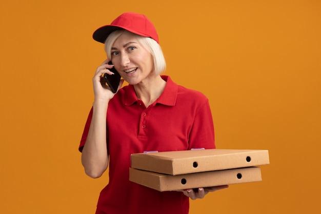 Vrolijke blonde bezorger van middelbare leeftijd in rood uniform en pet met pizzapakketten pratend over telefoon geïsoleerd op oranje muur met kopieerruimte