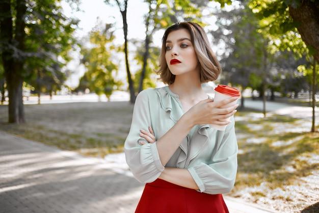 Vrolijke blonde in de parkbomen een kopje koffie rust