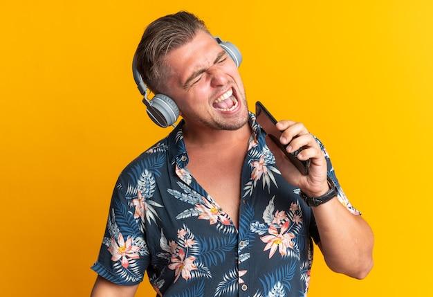 Vrolijke blonde knappe man op koptelefoon met telefoon dicht bij zijn mond zingen geïsoleerd op oranje muur met kopieerruimte
