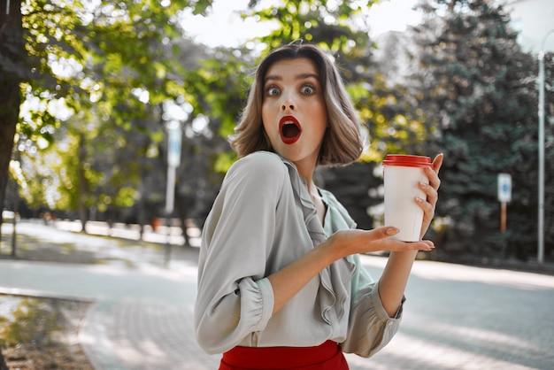 Vrolijke blonde met een kopje koffie buiten wandelen in het park
