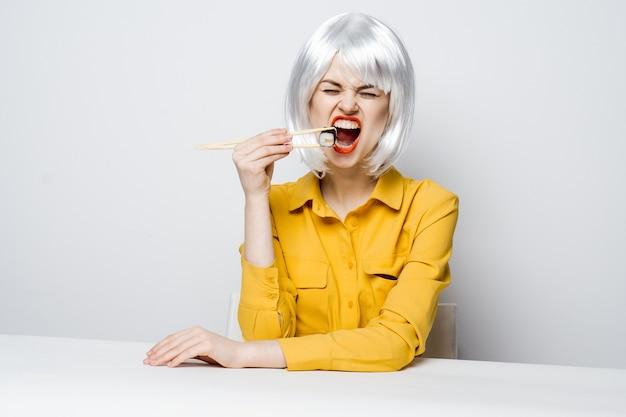 Vrolijke blonde met stokjes sushi eten aan tafel zitten
