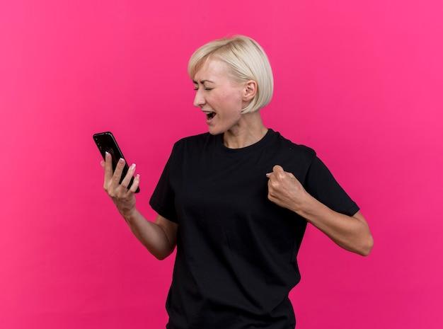 Vrolijke blonde slavische vrouw die van middelbare leeftijd mobiele telefoon houdt die ja gebaar met gesloten ogen doet die op karmozijnrode achtergrond wordt geïsoleerd
