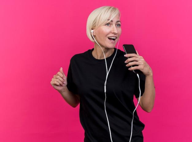Vrolijke blonde slavische vrouw van middelbare leeftijd dragen oortelefoons kijken kant houden van mobiele telefoon zingen geïsoleerd op karmozijnrode achtergrond met kopie ruimte