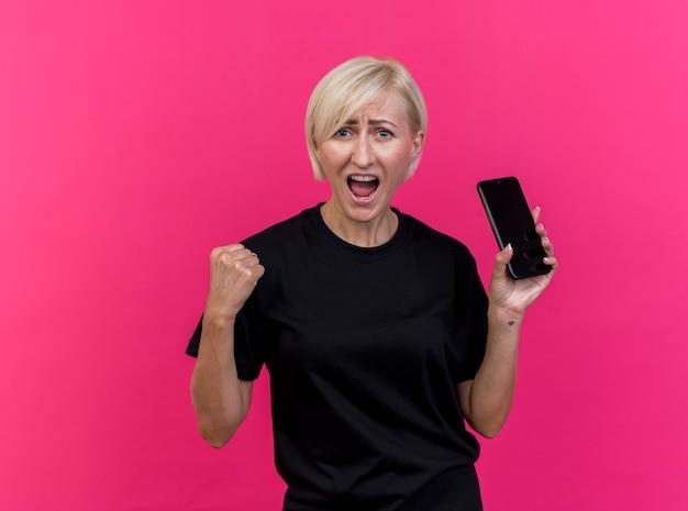Vrolijke blonde slavische vrouw van middelbare leeftijd kijken naar camera met mobiele telefoon doen ja gebaar geïsoleerd op karmozijnrode achtergrond met kopie ruimte
