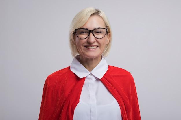 Vrolijke blonde superheld vrouw van middelbare leeftijd in rode cape met een bril glimlachend