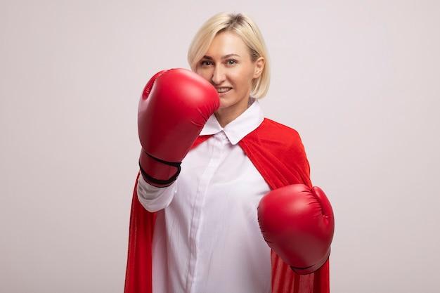 Vrolijke blonde superheldenvrouw van middelbare leeftijd in rode cape die bokshandschoenen draagt en vuisten in de lucht houdt