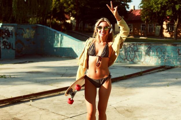 Vrolijke blonde tiener die haar skateboard
