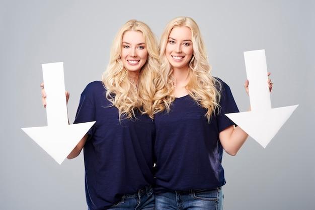 Vrolijke blonde tweeling en grote pijlen