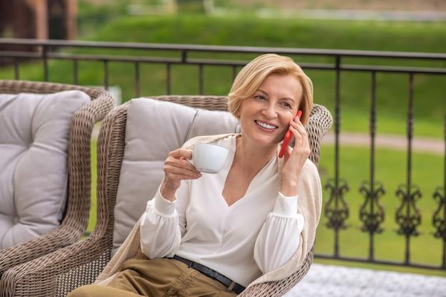 Vrolijke blonde vrouw belt op haar mobiel op het terras