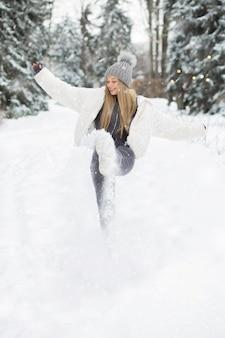 Vrolijke blonde vrouw die in het bos speelt tijdens de sneeuwval