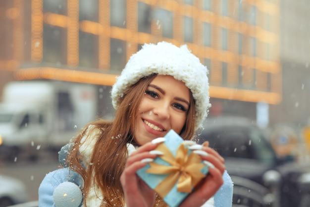 Vrolijke blonde vrouw draagt een witte gebreide muts met blauwe geschenkdoos, wandelen in de stad tijdens de sneeuwval snow