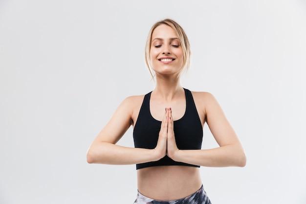 Vrolijke blonde vrouw gekleed in sportkleding uit te werken en te mediteren met handpalmen samen geïsoleerd over witte muur