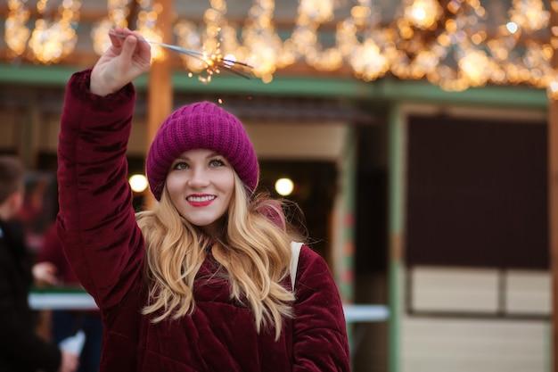 Vrolijke blonde vrouw gekleed in warme kleren, met gloeiende sterretjes op de kerstmarkt