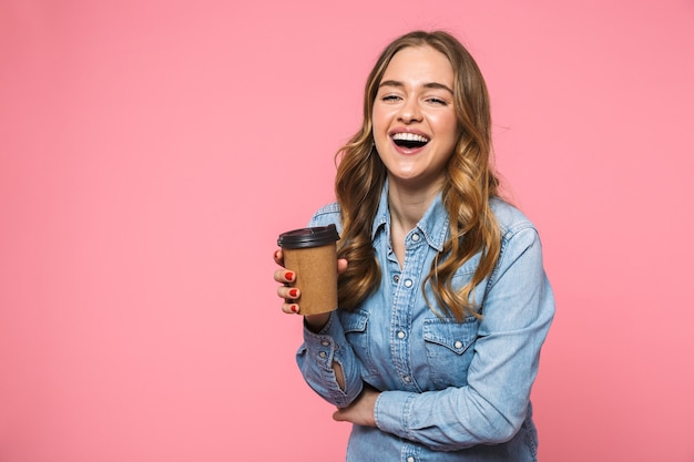 Vrolijke blonde vrouw in een denim shirt die koffie drinkt en naar de voorkant kijkt over de roze muur