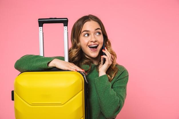 Vrolijke blonde vrouw in groene trui poserend met bagage en pratend door smartphone terwijl ze wegkijkt over roze muur