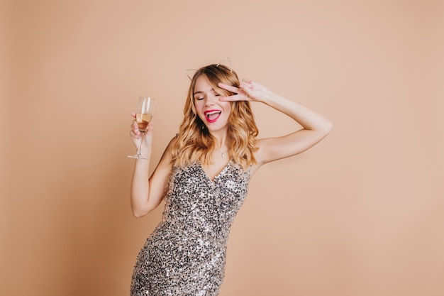 Vrolijke blonde vrouw in luxe jurk grappig dansen op feestje en champagne drinken