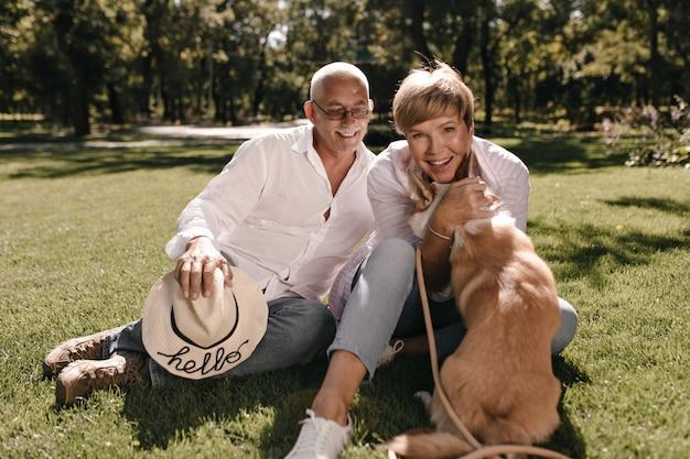 Vrolijke blonde vrouw in witte blouse en spijkerbroek glimlachend, hond knuffelen en zitten met grijze harige man met snor en hoed in shirt buiten.