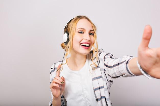Vrolijke blonde vrouw in witte trendy outfit poseren in grote koptelefoon lachen. krullend mooi meisje draagt gestreepte blouse luisteren muziek in nieuwe oortelefoons en plezier, dansen