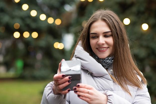 Vrolijke blonde vrouw met een geschenkdoos op straat. lege ruimte