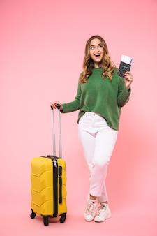 Vrolijke blonde vrouw met een groene trui die zich voorbereidt om te trippen met bagage en teken terwijl ze wegkijkt over de roze muur