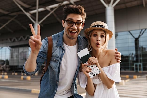 Vrolijke blonde vrouw met hoed maakt een grappig gezicht, houdt paspoort en kaartjes vast