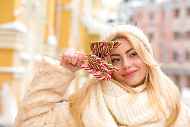 Vrolijke blonde vrouw met lang haar met een warme gebreide muts, met heerlijke kerstsnoepjes
