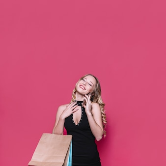 Vrolijke blonde vrouw met zakken die op telefoon spreken