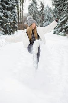 Vrolijke blonde vrouw speelt met sneeuw in het bos