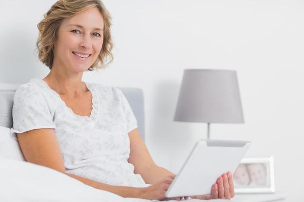 Vrolijke blonde vrouw zitten in bed met behulp van tablet pc