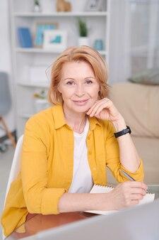 Vrolijke blonde zakenvrouw zittend door werkplek voor camera en het opschrijven van lijst met werkpunten tijdens het werken thuis