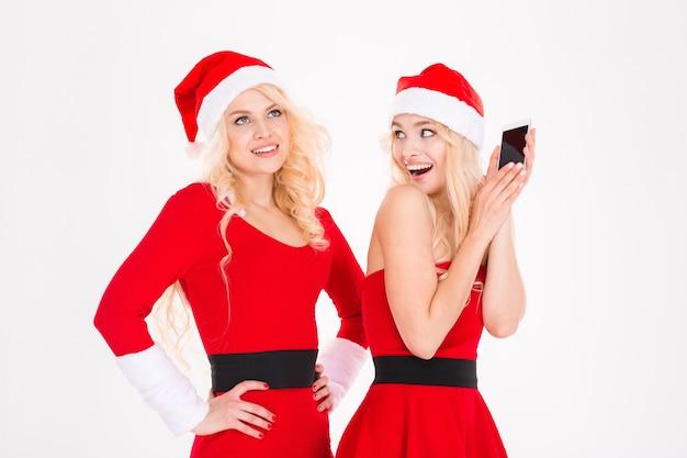 Vrolijke blonde zussen tweeling in rode kerstman kleding en hoeden verbergen poseren in de buurt van de kerstboom op witte achtergrond