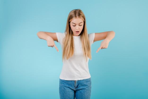 Vrolijke blondevrouw die vingers richten neer geïsoleerd over blauw