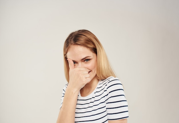 Vrolijke blondine op een lichte muur toont een vinger en een bijgesneden gestreept t-shirt is te zien