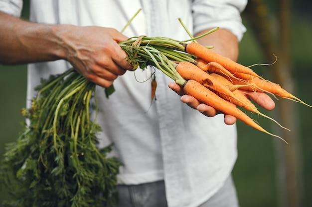 Vrolijke boer met biologische groenten in de tuin. biologische wortel in man's handen.