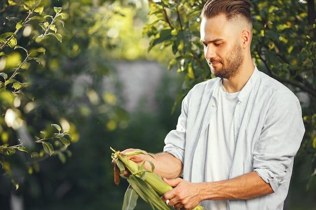 Vrolijke boer met biologische groenten in de tuin. gemengde biologische groente in man's handen.