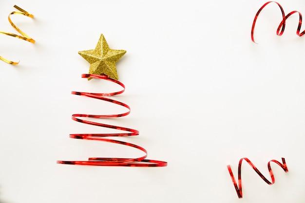 Vrolijke boom chistmas die van rood lint en gouden ster op witte achtergrond wordt gemaakt.