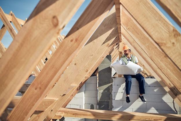 Vrolijke bouwer die beschermende uitrusting draagt en een blauwdruk van een nieuw gebouw vasthoudt