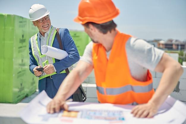 Vrolijke bouwmanager met een rol papier onder zijn arm glimlachend naar een bouwer