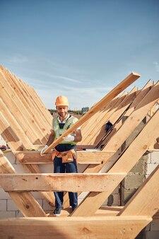 Vrolijke bouwplaatswerker die een lang stuk hout vasthoudt terwijl hij een dakframe bouwt