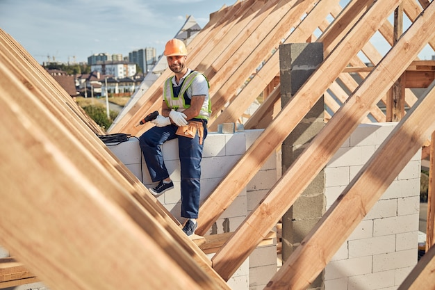 Vrolijke bouwvakker die beschermende uitrusting draagt en een boor vasthoudt terwijl hij op een muur zit en naar de camera kijkt