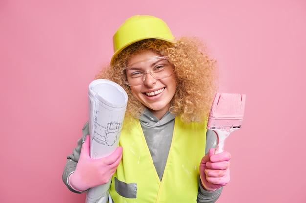 Vrolijke bouwvakker die in een goed humeur is, probeert haar architectonische plan in het leven uit te voeren, houdt een blauwdruk en een penseel vast voor het schilderen van muren draagt een beschermende helm en uniform