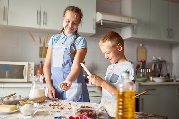 Vrolijke broers en zussen die deeg maken voor koekjes in een goed uitgeruste keuken
